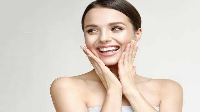 Woman smiling after applying facial cream