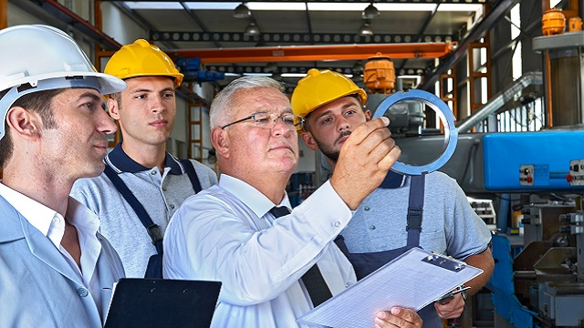 Workers performing an inspection to ensure compliance with quality standards