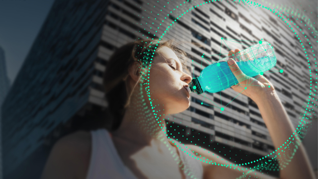 A girl drinking an energy blue drink from a botlle after running
