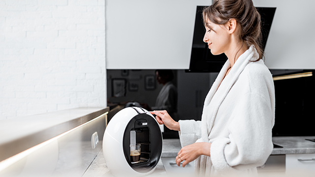 Innovation in Home Appliances - Woman in a home kitchen using a coffee machine to brew an expresso coffee.